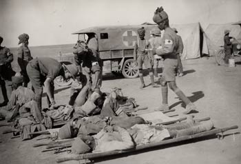 Indian medical orderlies attending to wounded soldiers on stretchers outside a dressing station, Mesopotamia, during the First World War.
