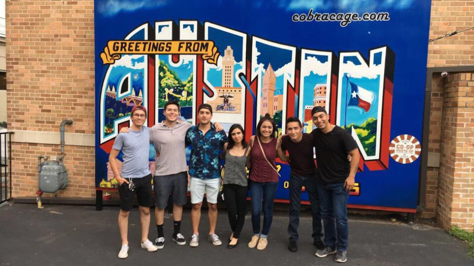 students standing in front of Austin wall mural