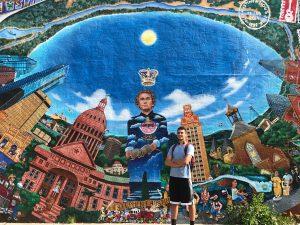 Isaac Gandara in front of Austin mural