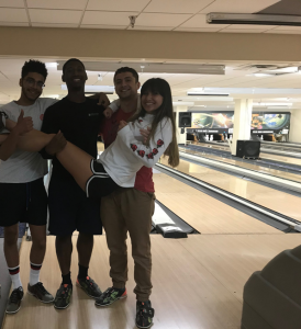 four students at the bowling alley, one is being carried by the other three