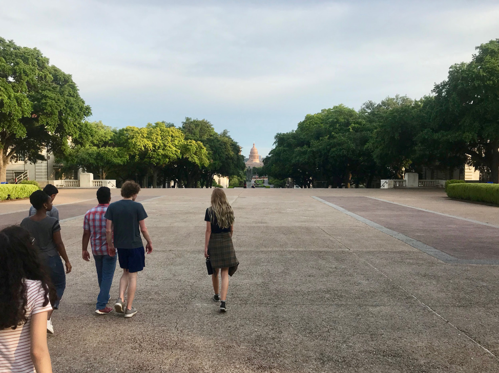 students walking on ut campus with capitol building in background