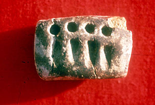 (Fig. 4)  Impressed tablet from Godin Tepe, Iran, ca. 3100 BC. courtesy Cuyler Young Jr.,  Royal Ontario Museum, Toronto. The small circular signs stand for 1 large measure of grain, the wedges for a small measure of grain.