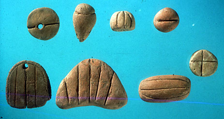 (Fig. 2) Tokens from Tello, ancient Girsu, present day Iraq, ca. 3300 BC. Starting above from left to right : 1 length of textile, one jar of oil, – ? –, one measure of wheat.  Continuing below from right to left: one ram, one length of rope, 1 ingot of metal, 1 garment. Courtesy Musee du Louvre, Department des Antiquites Orientales.