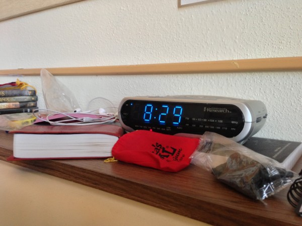 Digital clock showing 8:29 with books and other items on shelf