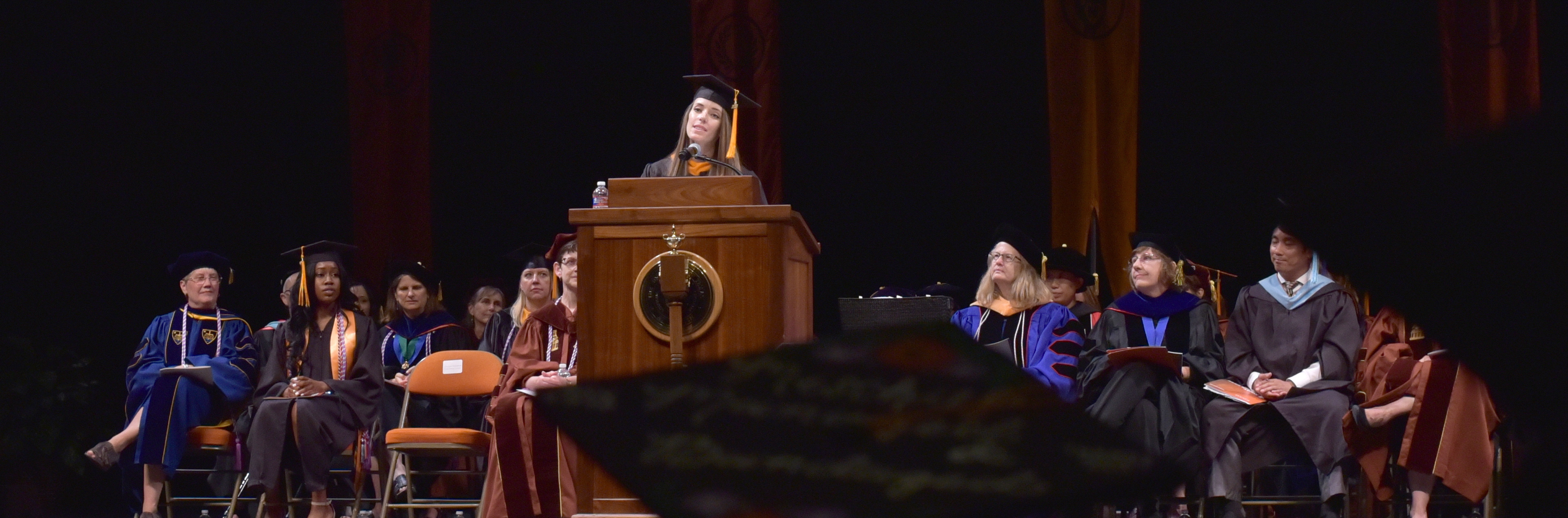 Graduate student speaking to graduating class