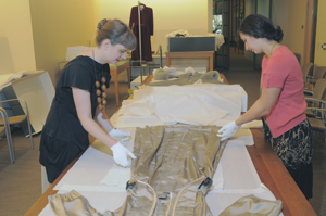 Jill Morena, Collection Assistant for Costumes and Personal Effects, and volunteer Emily Delheim prepare a film costume worn by Deborah Kerr in 'An Affair to Remember' (1957) to be repacked and returned to storage.  Five costumes were pulled for MFA students in Costume Technology in the Department of Theater and Dance.  The students examined the design, fabric choices, and construction techniques of the costumes. Photo by Pete Smith.