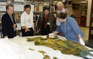 Ransom Center curators Steve Wilson (far left) and Jill Morena (second from right) discuss future collaboration with the university's School of Human Ecology to analyze fiber content and the construction history of the green curtain dress from 'Gone With The Wind.' University colleagues from Human Ecology include from left Dr. Bugao Xu; Professor in the Division of Textiles and Apparel, Dr. Kay Jay; Director of the Historical Textiles and Apparel Collection, Dr. Sheldon Ekland-Olson; Director of the school, and Nicole Villarreal; Human Ecology graduate student. Photo by Anthony Maddaloni.