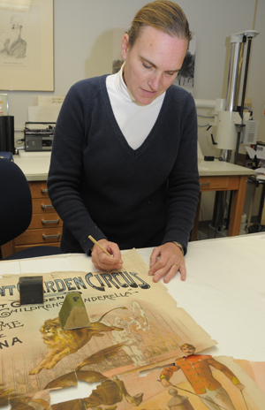 Volunteer paper conservator Lauren Morales shapes a toned insert paper to fill in the losses of an original 1889 English circus poster, part of the performing arts collection. The losses (white spaces) are visible in the area of the horse (lower left of the image along a horizontal fold line) and around the orange-colored insert for the man's jacket. Photo by Anthony Maddaloni.