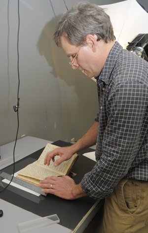 Hal Erickson, a University of Utah Health Sciences Center researcher, visited the Ransom Center to apply nondestructive forensic techniques for recovering faded, erased, redacted, obscured or otherwise lost content.  Here, Erickson is photographing a passage that was redacted, and then further obscured with adhered paper bearing replacement text, by Thomas Hammond in a manuscript volume of his 'Memoirs.'  Photo by Anthony Maddaloni.