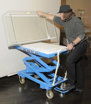 Wyndell Faulk, preparator with the Ransom Center's exhibition services, works to de-install the exhibition 'Discovering the Language of Photography: The Gernsheim Collection.'  Photo by Pete Smith.
