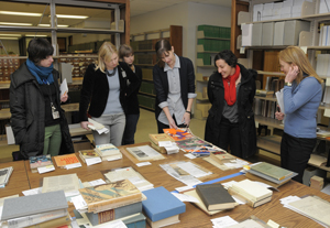 Curator of Academic Affairs Danielle Sigler (center) shares collection items for 'Banned, Burned, Seized, and Censored,' a 2011 fall exhibition that examines the multi-faceted machinery of literary censorship during the inter war years. Photo by Anthony Maddaloni.