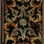 """""""Officium Beatae Mariae Virginis"""" (Venice: Paulus Balleonius, 1709). Dedicated to the Virgin Mary, this devotional is bound in thin wooden boards held together by metal hinges. The delicate fronds and flourishes on the upper and lower covers were created by inlaying various colored woods into a black veneer. Some of these woods are stained blue and green, while others retain their natural colors. The mother-of-pearl dog-roses that adorn the covers and spine are a symbol of Mary, and thus function as both ornament and clue to the book's content. Photo by Pete Smith."""