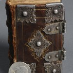 """The New Testament of Our Lord Jesus Christ"" (London: Christopher Barker, 1598). The Stark Library. Early pocket-sized Bibles often benefitted from the protection of clasps and cornerpieces, which protected a volume's edges from wear, enhancing longevity and portability. This small New Testament volume, printed by the same printer as the ""Book of Common Prayer,"" belonged to a wealthy individual: the edges of the pages show the remains of gilding, while the clasps and cornerpieces appear to be genuine silver. The Tudor roses visible on the cornerpieces and an inscription by a previous owner on the inside cover may link the book to Queen Elizabeth I. Photo by Pete Smith."