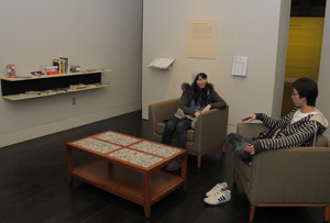 Students in the 'Culture Unbound' exhibition, specifically in the reading nook filled with books featured in the exhibition. Photo by Anthony Maddaloni.