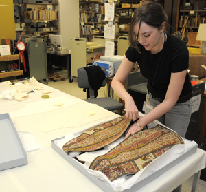 Volunteer Kathleen Dowling handles a vest from the Gertrude Stein personal effects collection, working to create custom interior supports for the vest for display. Photo by Anthony Maddaloni.