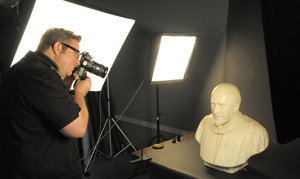 Photographer Anthony Maddaloni shoots an image of a plaster maquette of a bust of W. E. B. DuBois. Photo by Pete Smith.