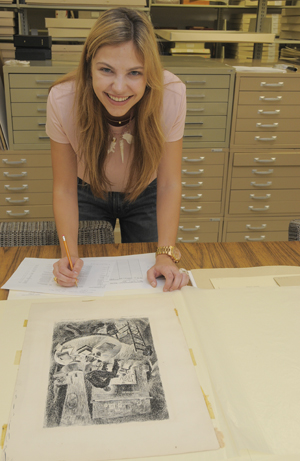 Broadcast journalism and radio-television-film major Isabella Ferraro, a student worker in the Ransom Center's art collection for the past two years, helps realign the flat files in the prints and drawings room. Photo by Anthony Maddaloni.