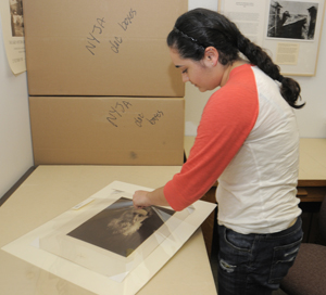 Freshman Elizabeth Diaz, a student worker, assists in housing photographs, including this Julia Margaret Cameron image from the Gernsheim collection. Photo by Anthony Maddaloni.