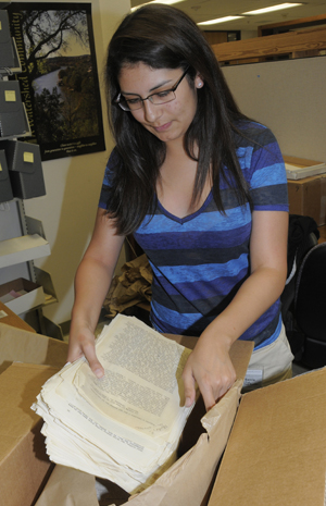 Government and German major Caren Garcia, a second year student working in the Ransom Center's archives and visual materials cataloging department, assists with processing the Clancy Sigal papers. Photo by Anthony Maddaloni.