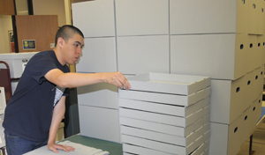 Junior Isaac Benavidez, an English major and student worker at the Ransom Center, assembles archival boxes for collection storage. Photo by Anthony Maddaloni.