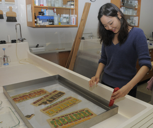 Inkyung Youm, a third-year graduate conservation intern at the School of Information at The University of Texas at Austin, measures the pH of an alkaline water bath for a fragmented circus poster from the Ransom Center's performing arts collection. Photo by Anthony Maddaloni.