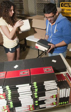 Albert Palacios, assistant to the curator of film, and Elizabeth Salazar, film collection volunteer, inspect an incoming collection of audio tapes of radio dramas from the 1950's and 60's. Photo by Pete Smith.
