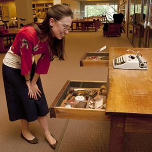 Meagan Samuelsen, a volunteer with costumes and personal effects, looks at John Fowles's writing desk, complete with its contents. The desk will remain on display for at least the next two years in the Ransom Center's Reading and Viewing Room. Photo by Pete Smith.