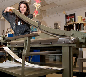 Volunteer Emily Butts, a high school senior at St. Andrew's Episcopal School, uses the Vagelli board shear to cut paper and board to rehouse single leaves of handwritten documents, many on parchment, in the Center's Medieval and Early Modern Manuscript Collection. Photo by Pete Smith.