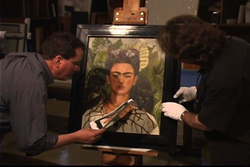 Exhibition Conservator and Head of Exhibition Services Ken Grant and Preparator Wyndell Faulk inspect Frida Kahlo's 'Self-portrait with Thorn Necklace and Hummingbird' in 2009.