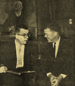 William Todd and F. Warren Roberts discuss a rare book beneath a portrait of George Bernard Shaw, ca. 1961. Unidentified photographer.