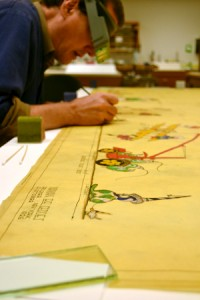 Conservator Ken Grant works in the paper lab, consolidating the paint layer on designer Norman Bel Geddes's 1926 drawing for floats and participants in Macy's parade. The drawing will be included in an upcoming exhibition on Bel Geddes, with support generously provided by an FAIC/Tru Vue Optium® Conservation Grant. Photo by Kelsey McKinney.