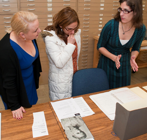 Helen Adair shows Maggie Cino and Faye Lane a notebook from Spalding Gray's archive. Photo by Pete Smith.