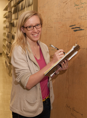 Undergraduate intern Kelsey McKinney with the authors' door at the Ransom Center. Photo by Pete Smith.