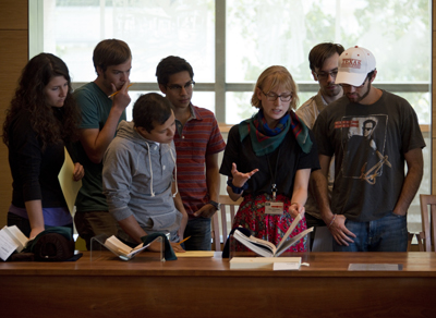 """Graduate intern Jenn Shapland, center, shares annotated books from Wallace's library and research materials he used while writing """"Infinite Jest."""" Photo by Pete Smith."""