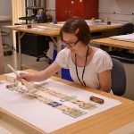 """Head of Paper Conservation Heather Hamilton treats an animated Movie Jecktor scroll for the exhibition on """"Alice in Wonderland."""" Photo by Alicia Dietrich."""