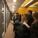"""Guests view photographs at the pop-up exhibition at the Ransom Center with images from Alec Soth and Brad Zellar's """"Texas Triangle"""" project. Photo by Pete Smith."""