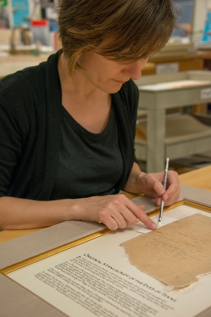 Conservator Heather Hamilton puts the finishing touches on the manuscript treatment. Photo by Pete Smith.