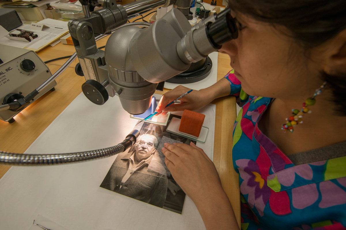 Conservator consolidating a crack in the gelatin emulsion layer of the photograph. Photo by Pete Smith. /  Restauradora consolidando una grieta en la emulsión de gelatina de la fotografía. Fotografía por Pete Smith.