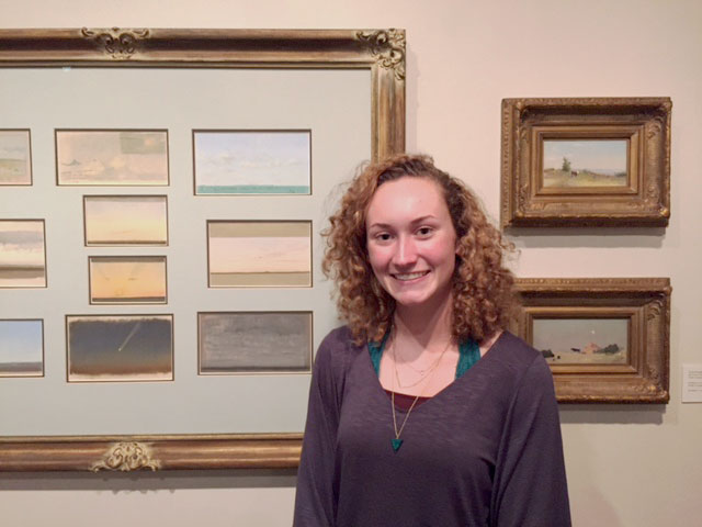 "Isabella Savage in front of her favorite section of Frank Reaugh: Landscapes of Texas and the American West, ""Studie and Sketches."""