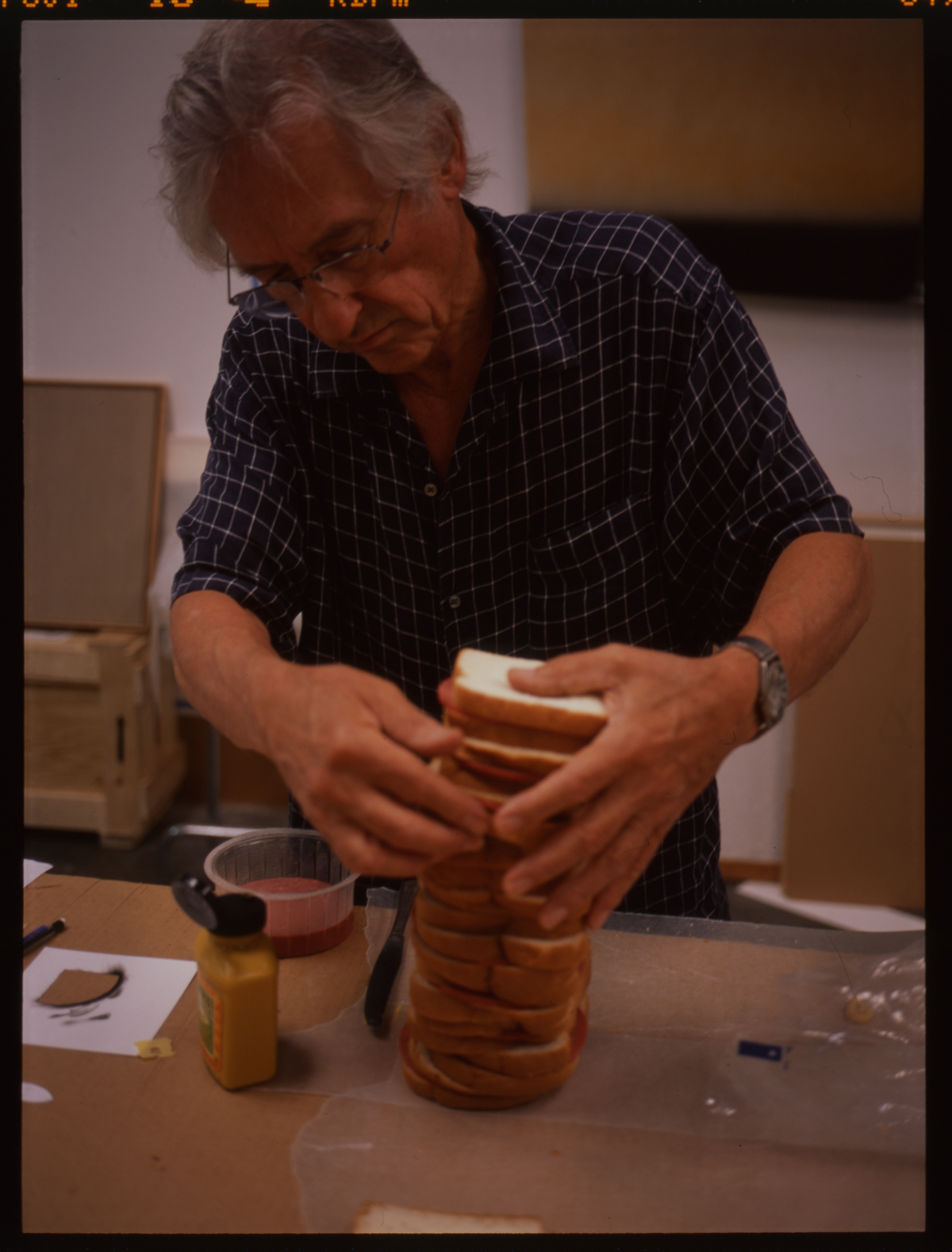 Ed Ruscha (American, b. 1937), Ed Ruscha making a sandwich to be photographed for his book On the Road: An Artist Book of the Classic Novel by Jack Kerouac, ca. 2008 or 2009. Color transparency, 4 x 5.6 cm. © Ed Ruscha. For Ruscha's most recent book project, published in 2009, he created an illustrated version of Jack Kerouac's seminal beat novel On the Road. The complete text of the novel is reproduced alongside photographs Ruscha made or selected from other sources. Several boxes of material document the process from conception to publication, and include contact sheets, negatives, and transparencies for all the images from the book that Ruscha made himself (including this sandwich), as well as a few that didn't make the cut.