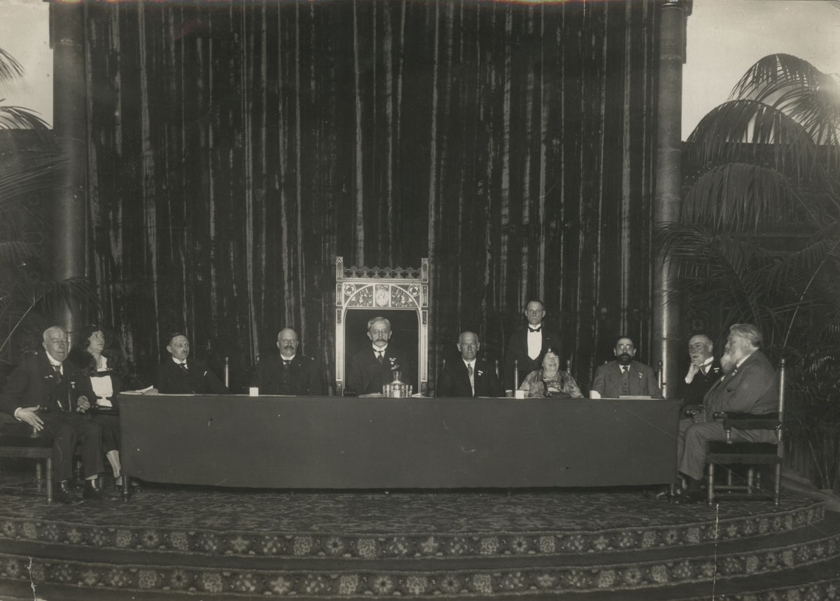 Unidentified photographer. Photograph taken at the PEN Congress in Holland, 1931; seated to the right of the podium are PEN president John Galsworthy and PEN founder Amy Catherine Dawson-Scott.