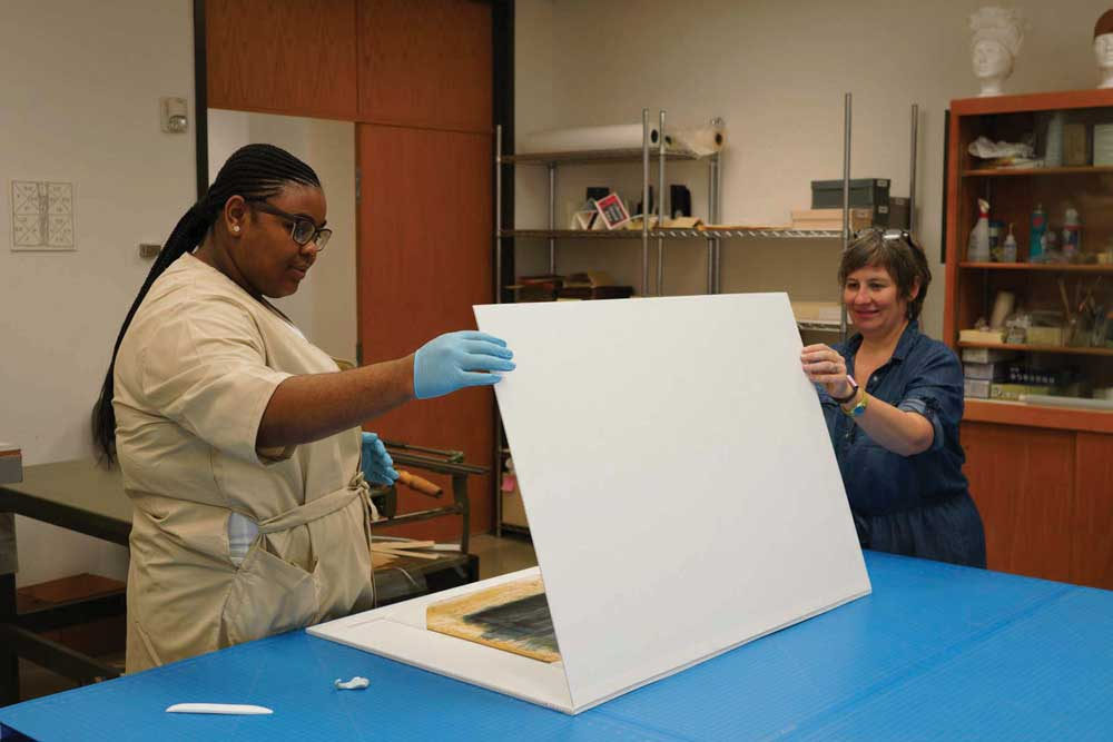 Preservation technician Genevieve Pierce and I work on sink mats for storyboards from the David O. Selznick collection.