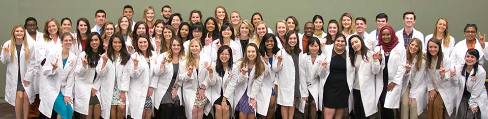 a group of students in white lab coats doing the Hook Em sign
