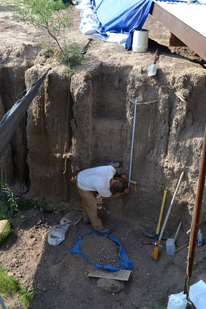 Sam Cason collecting sediment samples for snail recovery at the Genevieve Lykes Duncan site, on the 02 Ranch in Brewster County. This 2.8 meter high column in the arroyo wall runs from the modern ground surface to a level estimated at about 10,200 radiocarbon years before present. Excavations in the Paleoindian deposits are ongoing just out of view to the right, at about the same level where Sam is working. One of the completed sample bags can be seen at lower right (average weight, 15. 5 kilograms, or 34 pounds).