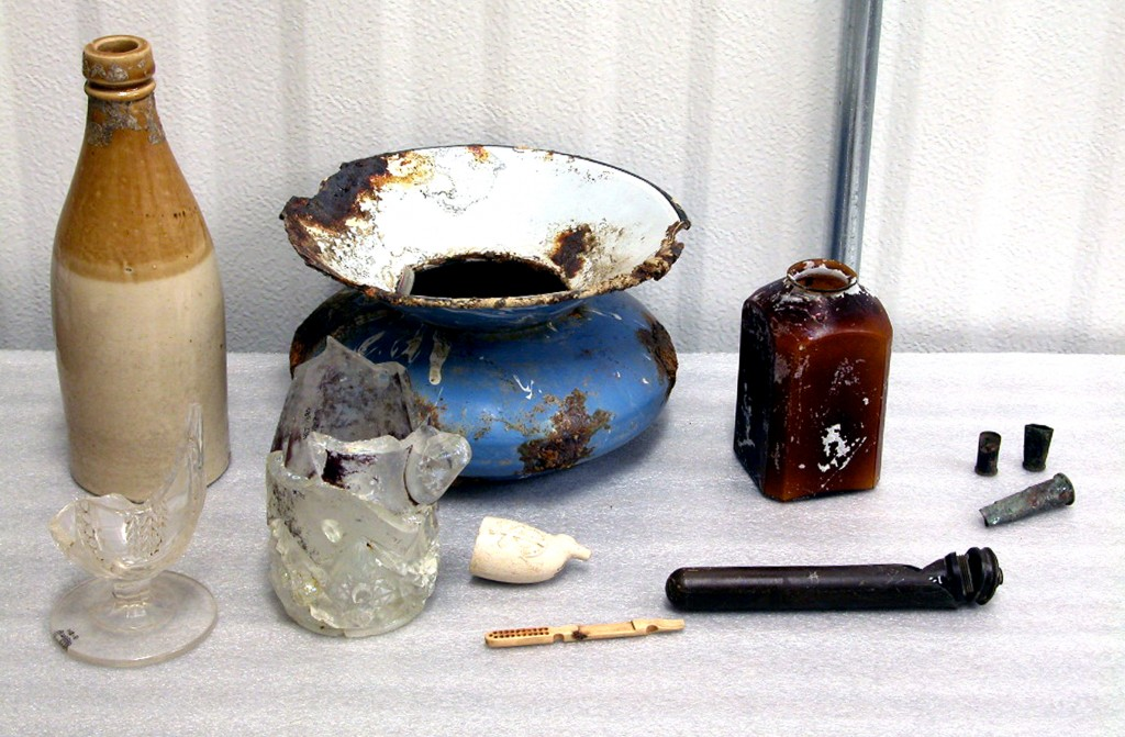 This small sample of the thousands of artifacts recovered from excavations in Austin's 19th-century Guytown district reflects the area's notorious past. Shown in clockwise order are a stoneware ale bottle, blue and white spittoon, an amber snuff jar, cartridge casings, a vaginal syringe (perhaps belonging to one of the area's prostitutes), a bone handle of a makeup brush, a ceramic pipe bowl with anchor motif, and fragments of a fancy glass mug and goblet. TARL Collections; photo by Kerri Wilhelm.
