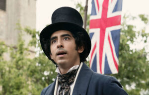 Movie still of Ango-Indian actor Dev Patel as David Copperfield, wearing a tall hat standing in front of a Union Jack