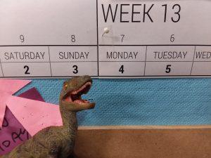 Toy velociraptor posed in front of calendar