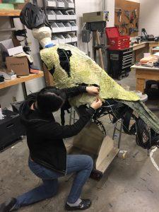 Student applying skin to raptor body