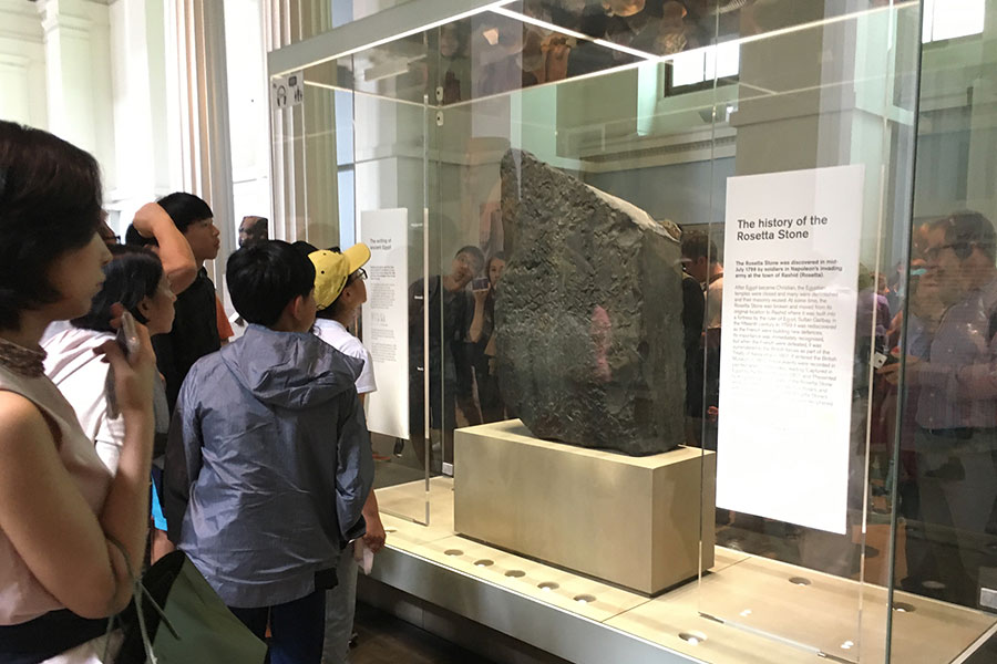 people standing in front of Rosetta Stone