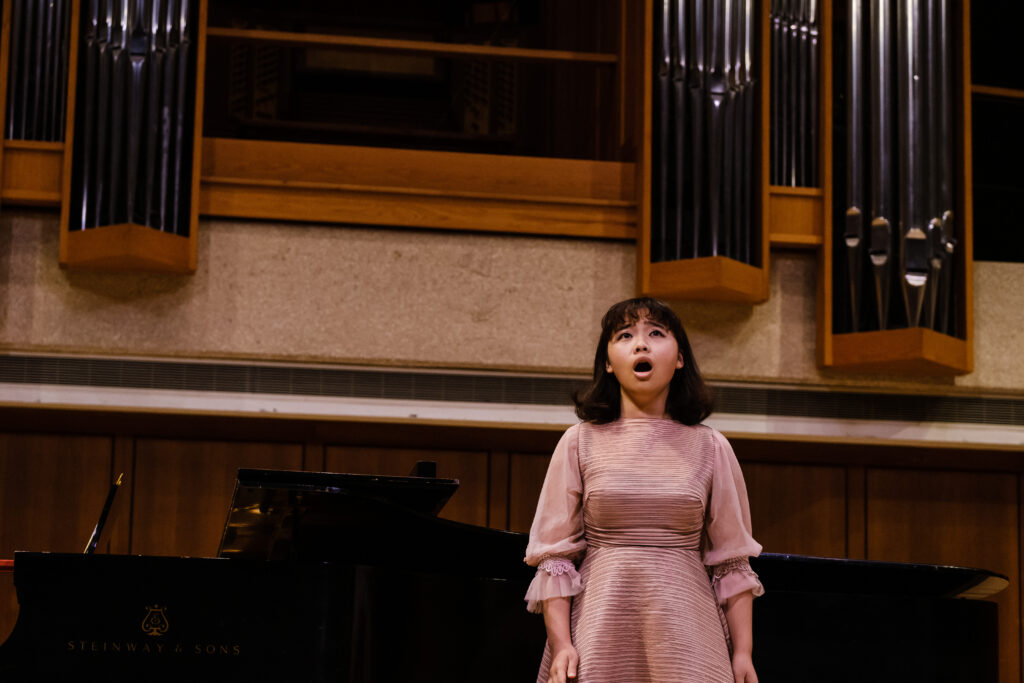 Student singer stands next to the piano while singing